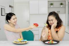 Den överviktiga kvinnan vägrar att äta donuts Royaltyfri Foto
