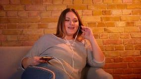 Den överviktiga långhåriga kvinnliga modellen sitter på soffan som lyssnar till musik i hörlurar i hemtrevlig hem- atmosfär lager videofilmer