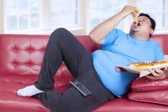 Den överviktiga mannen äter pizza Royaltyfria Foton