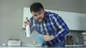 Den överviktiga mannen besprutar hans tvättmedel på tabellen Den pösiga grabben gör ren hans kök med servetten från smuts, fett o stock video