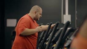 Den överviktiga mannen med stark beslutsamhet arbetar i idrottshall är på den feta buken stock video