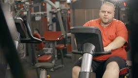 Den överviktiga mannen utbildar på cykeln på konditionklubban