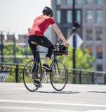 Den Сyclist grabben föredrar cyklar som ett ekologiskt medel, och ritter cyklar ner stadsgatan arkivbild