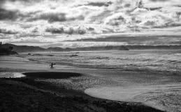 Den abstrakta ensamma surfaren skriver in vatten på Morro vaggar med molnhavet royaltyfria foton