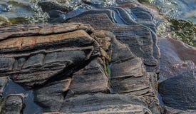 Den abstrakta förbluffa ursnygga detaljerade sikten av den naturliga stenen vaggar yttersidasammanträde i sjövatten Royaltyfria Bilder