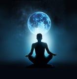 Den abstrakta kvinnan mediterar på den blåa fullmånen med stjärnan i mörk natthimmel