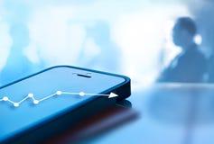 Den abstrakta mobiltelefonen och grafen kartlägger tillväxt på skärmen, och bakgrund för affärsmannen, blått tonar stil Royaltyfri Bild