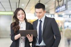 Den affärsmanen och kvinnan diskuterar arkivfoton
