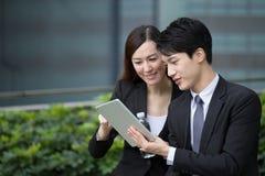 Den affärsmannen och kvinnan diskuterar finansiellt plan på siffra Royaltyfria Bilder