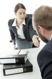 Den affärsmannen och kvinnan frågar att sitta ner Arkivfoto