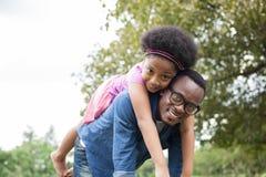 Den afrikansk amerikanfadern och dottern som spelar och bär på, drar tillbaka i gräsplan parkerar plats royaltyfria bilder