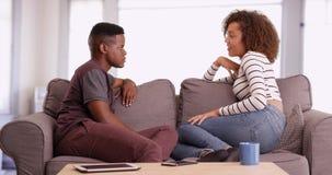 Den afrikansk amerikanmannen och kvinnan talar, medan koppla av på deras soffa i deras vardagsrum royaltyfria bilder