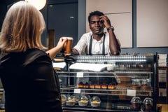 Den afrikanska baristaen ger den beställde kaffekunden av den moderna coffee shop arkivfoto