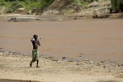 Den afrikanska flickan går på flodbanken Arkivbilder