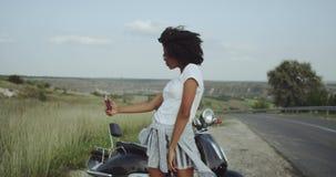 Den afrikanska flickan med lockigt afro- hår tar selfies i den härliga naturen som älskar den vibe lager videofilmer