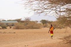 Den afrikanska kvinnan från den Samburu stammen släkt Masaistammen i nationell dräkt går på savann royaltyfri fotografi