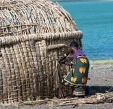 Den afrikanska kvinnan gör den traditionella kojan Royaltyfria Bilder