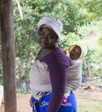 Den afrikanska kvinnan med behandla som ett barn i en rem Royaltyfri Bild