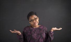 Den afrikanska kvinnan med vet jag inte gest på svart tavlabakgrund Royaltyfria Bilder