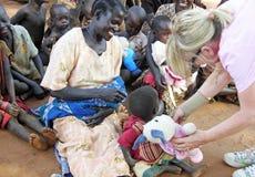 Den afrikanska kvinnan som fylls med glädje, när hon behandla som ett barn barnet, erbjuds en gåva Fotografering för Bildbyråer