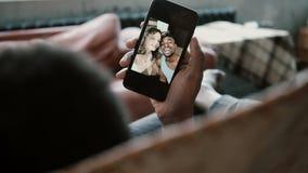 Den afrikanska mannen använder Smartphone, ser foto med den Caucasian flickvännen Man och kvinna som kysser, ler och skrattar Royaltyfria Bilder
