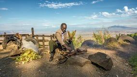 Den afrikanska mannen i en dräkt säljer havre nära den stora Rift Valley in Arkivfoto