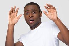Den afrikanska mannen som ser kameran, g?r stora ?gon k?nner sig f?rskr?ckt arkivfoton