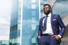 Den afrikanska millenial mannen i dräkten som står nära kontorsbyggnaden, fyllde med tacksamhet med kopieringsutrymme royaltyfria foton