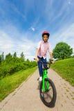 Den afrikanska pojken i röd hjälm rider ljust - den gröna cykeln Royaltyfria Foton