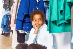 Den afrikanska pojken med handen på kind borrade shoppar in Arkivbild