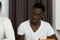 Den afrikanska studenten sitter på tabellcloseupen Royaltyfri Fotografi