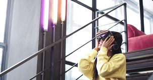Den afrikanska unga kvinnan imponerade mycket att spela med exponeringsglas för en virtuell verklighet i ett modernt kontor, henn arkivfilmer