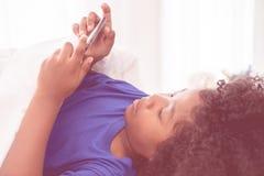 Den afrikanska ungen spelar med smartphonen på säng arkivbild