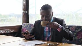 Den afro- amerikanska affärsmannen skriver ett meddelande på smartphonen arkivfilmer