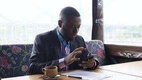 Den afro- amerikanska affärsmannen skriver ett meddelande på smartphonen som sitter i kafé arkivfilmer