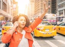 Den afro- amerikanska kvinnan som kallar en taxi i New York nära, tajmar det fyrkantiga området Arkivfoto