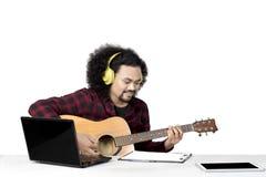 Den afro- mannen spelar en gitarr på studion royaltyfri fotografi
