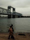 Den afro- studenten och vitflickan på går på den sandiga flodstranden i höst Royaltyfria Bilder