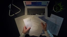 Den aggressiva mannen kastar dokument och tar hans huvud som sitter på tabellen med en bärbar dator i aftonen lager videofilmer