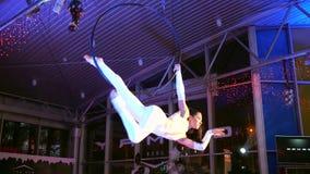Den akrobatiska showen, den böjliga flickan balanserar på gymnastiskt beslag i luft på aftonhändelsen stock video