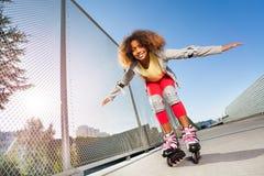 Den aktiva afrikanska flickan som rollerblading på skridskon, parkerar royaltyfri fotografi