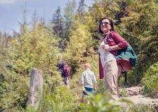 Den aktiva familjen går i bergskog arkivbild