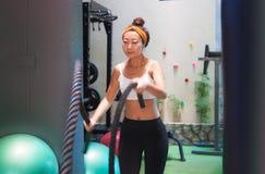 Den aktiva flickan gör övning med konditionrepen i idrottshallen royaltyfria bilder