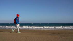 Den aktiva fotvandrarekvinnan går på stranden Caucasian ung kvinna med ryggsäcken på Tenerife, kanariefågelöar, Spanien stock video