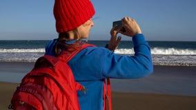 Den aktiva fotvandrarekvinnan går på stranden och gör fotoet på hennes smartphone Caucasian ung kvinna med ryggsäcken på Tenerife stock video
