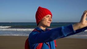 Den aktiva fotvandrarekvinnan går på stranden och gör självfotoet på hennes smartphone Caucasian ung kvinna med ryggsäcken på lager videofilmer