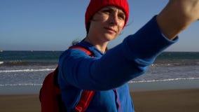 Den aktiva fotvandrarekvinnan går på stranden och gör självfotoet på hennes smartphone Caucasian ung kvinna med ryggsäcken på arkivfilmer