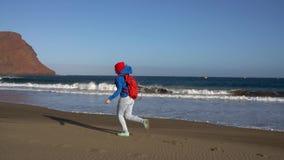 Den aktiva fotvandrarekvinnan kör och hoppar på stranden Caucasian ung kvinna med ryggsäcken på Tenerife, kanariefågelöar, Spanie arkivfilmer