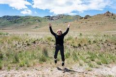 Den aktiva höga vuxna kvinnan hoppar för glädje i en äng i antilopödelstatspark arkivbilder