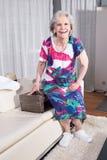 Den aktiva kvinnliga pensionären packar tappningresväskan för sommarsemester Royaltyfri Foto